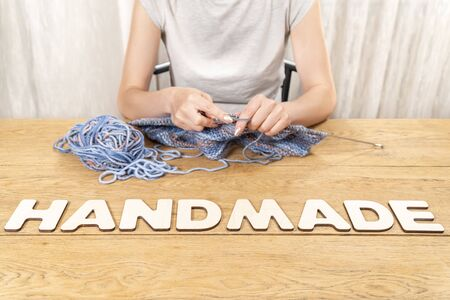 word handmade is laid out in wooden letters on an old wooden table where a woman knits