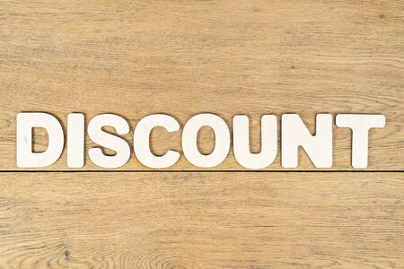 Word - discount, laid out letters on an old wooden oak table