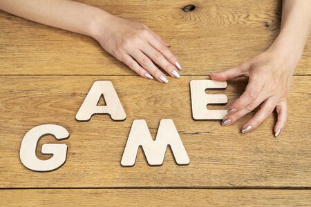 woman sitting on a chair at the table laid out the word game of wooden letters
