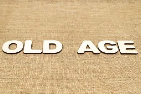 phrase - old age is laid out in wooden letters on the old brown sacking