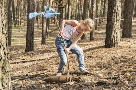 child found an unexploded rusty bomb in the forest and sets a mark near it Stok Fotoğraf