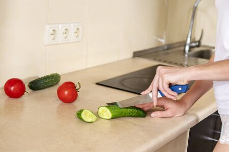 female hands with a knife cut cucumber on the kitchen table