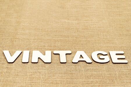 word - vintage is laid out in wooden letters on the old brown sacking