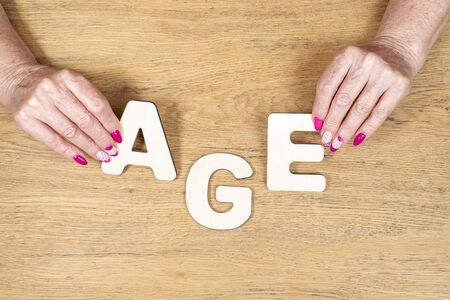 word age, spread out of wooden letters with old female hands with a manicure