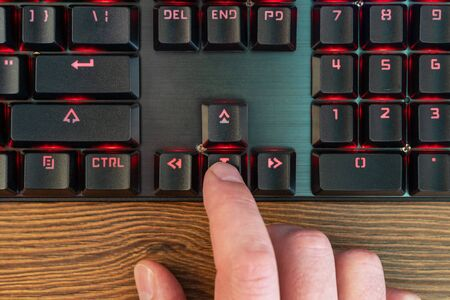 male hand finger presses the down arrow on the keyboard lying on a wooden table, close-up