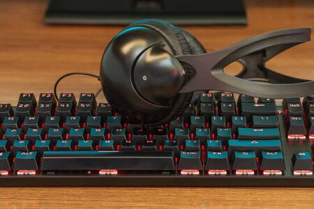 large black headphones on the keyboard with blue backlight