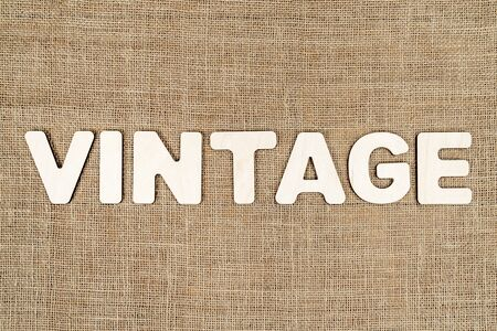 word - vintage is laid out in wooden letters on the old brown canvas