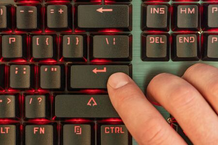 Male hand presses enter key on black keyboard with red backlight