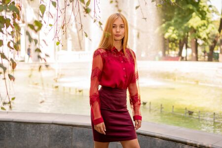 portrait of a beautiful girl in red clothes on a background of a blurred fountain in the park Banco de Imagens