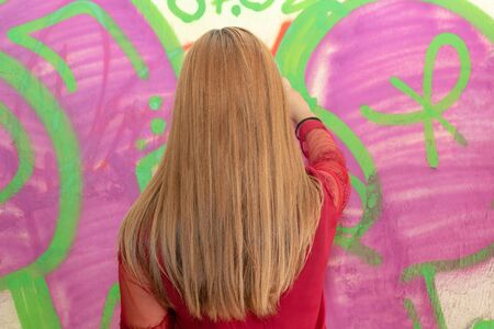 girl in red draws spray can on the wall, rear view
