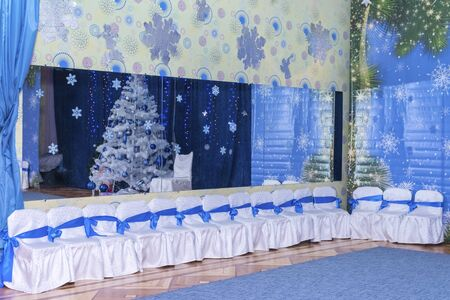 Hall kindergarten decorated in blue tones for the Christmas holiday. With a large mirror and children chairs