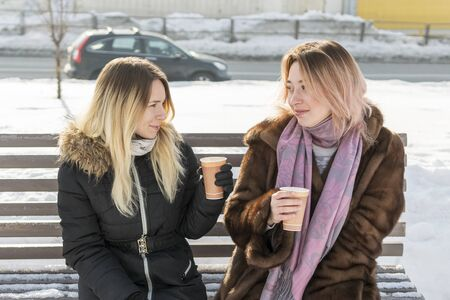 two women drink coffee with paper cups sitting on a bench in winter