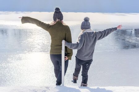 two women want to go on the ice of a frozen river in winter