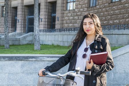 portrait of a beautiful female student with a book in her hand holding the wheel of a bicycle against the background of the university building