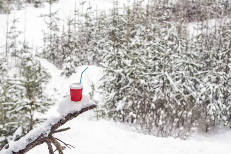 red coffee cup and straw on the snow-covered driftwood against a blurred forest