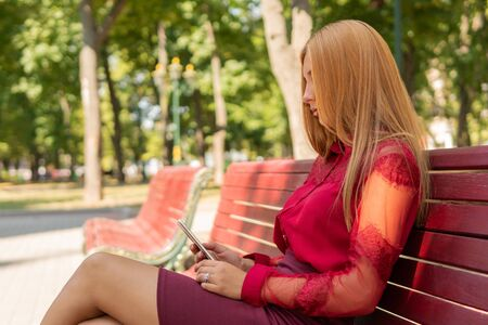 beautiful girl sitting on a bench in the park looks at her phone