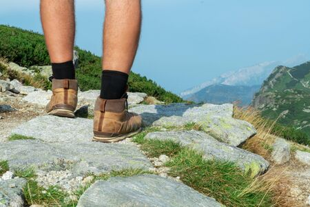 legs of a tourist in trekking boots close-up on a rock on a background of mountains, rear view