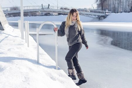 beautiful woman goes down on the ice of a frozen river holding on to the rail