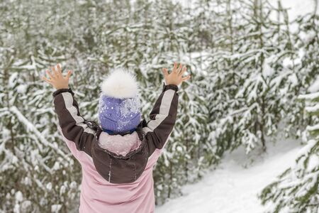 child is standing with raised hands on the background of a snowy forest, his back to the camera Banco de Imagens