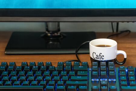 cup of coffee near a black keyboard with backlight on a wooden table Banco de Imagens