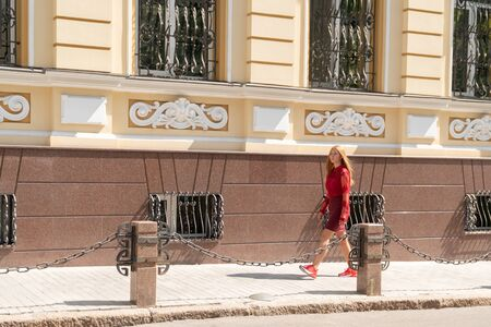 beautiful woman in red clothes walks along the sidewalk along an old building