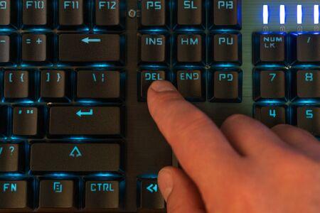 finger of a male hand presses the delete key on the backlit keyboard Reklamní fotografie