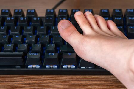 Children foot on a black keyboard with blue backlight