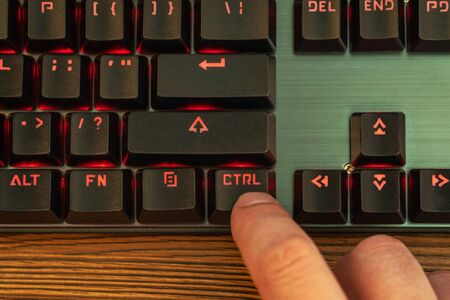 index finger of a male hand presses the control key on a black keyboard