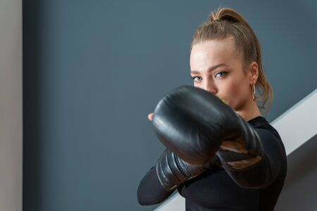 portrait of a beautiful athletic woman in boxing gloves in a protective pose 免版税图像