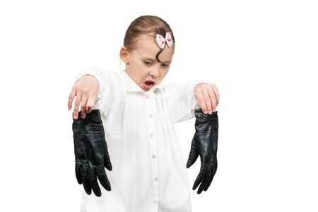 little girl took off her gloves and looks at them with contempt isolated on a white background