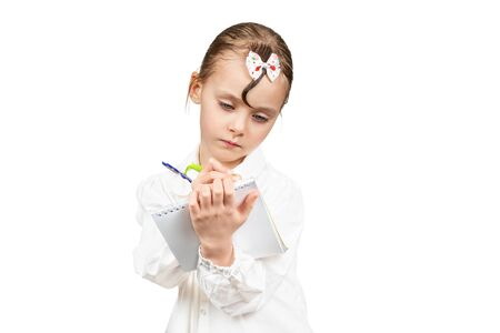 Little beautiful girl writes in a notebook while holding it in her hands isolated on white background Фото со стока