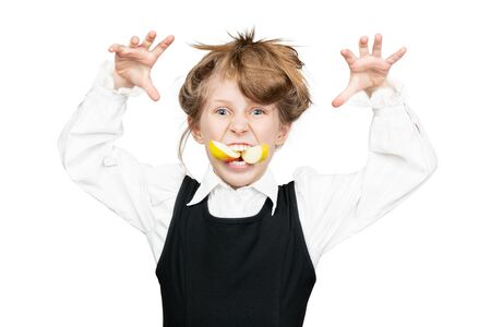 shaggy schoolgirl in uniform grimaces with an apple in her mouth isolated on white background