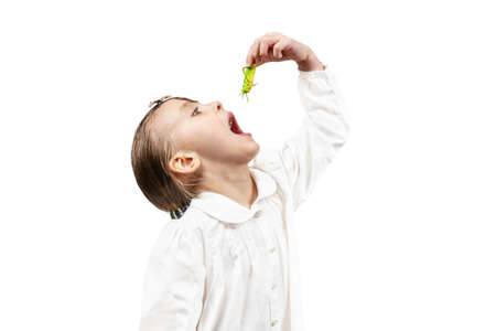 little beautiful girl opened her mouth to eat a green grasshopper isolated on white background Imagens