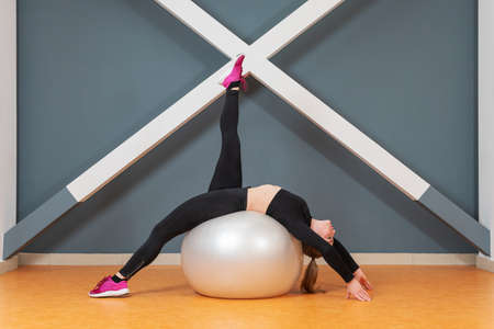 Woman stretching while standing on a bridge on a fitness ball 版權商用圖片