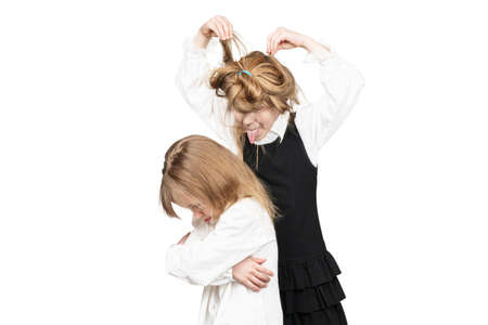 Older shaggy sister teases upset little sister writhes her faces behind her back isolated on white background