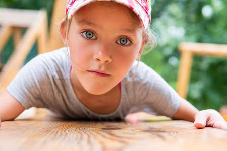 Portrait of a little girl in a cap lying on her stomach on a wooden board in the park, close-up. Child girl with big blue eyes.