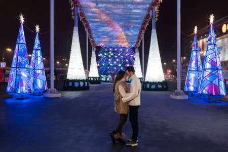 couple in love at night on a square decorated with lamps on Christmas Eve Standard-Bild