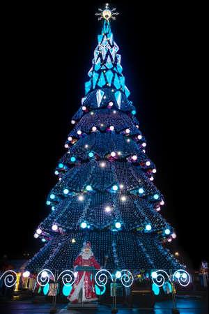 big sparkling city christmas tree at night with Santa Claus at the base Standard-Bild