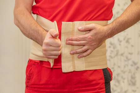 man in red clothes with a sore back puts on an orthopedic belt for his back