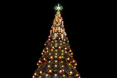 beautiful city christmas tree at night with luminous garlands on a black background