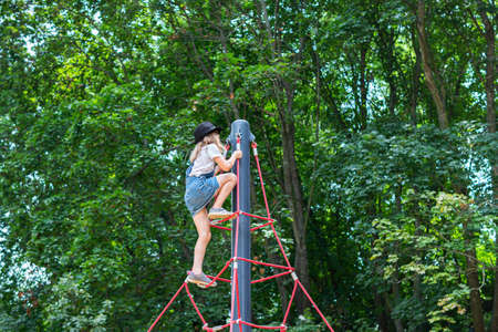 child girl in a skirt and hat climbs up the rope pyramid to the playground Standard-Bild