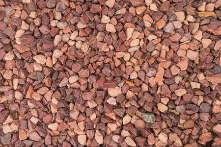brown gravel with small twigs, blades of grass and leaves as grunge background
