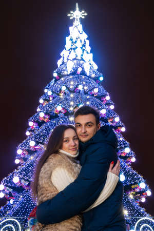 guy and girl are hugging on the background of the city Christmas tree