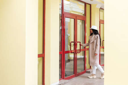 Business woman in coat and white hat enters the building holding the door handle
