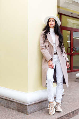 Portrait of a beautiful brunette woman in a coat and white hat leaning on a column