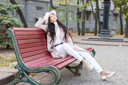 Beautiful woman in a coat and hat with pleasure sits on a bench on a city street Standard-Bild