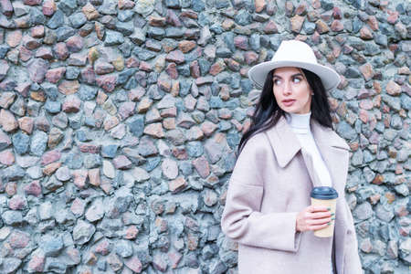 portrait of a beautiful woman with a cup of coffee in her hand near a stone wall