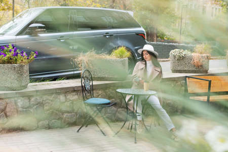Woman with phone and a cup of coffee in a cafe on the street, shot through the foliage