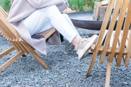 A woman in a coat and sneakers sitting on a chair leaned her leg on another chair, close-up