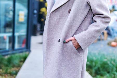 Woman hand in a coat pocket, close-up. Thumb peeks out of coat pocket Standard-Bild